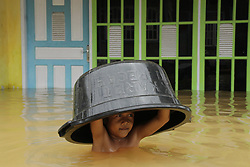 March 7, 2017 - Kampar, Riau, Indonesia - A young boy caries a basin on his head, while he walks through the heavily flooded streets of Buluh Cina village in Indonesia. Heavy rains continue to cause floods forcing hundreds of people to evacuate their homes. (Credit Image: © Ahmad Widi/Sijori Images via ZUMA Wire)