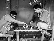 18 JULY 2013 - BANGKOK, THAILAND: Motorcycle taxi drivers play chess while they wait for fares on Sukhumvit Soi 79 in Bangkok.       PHOTO BY JACK KURTZ