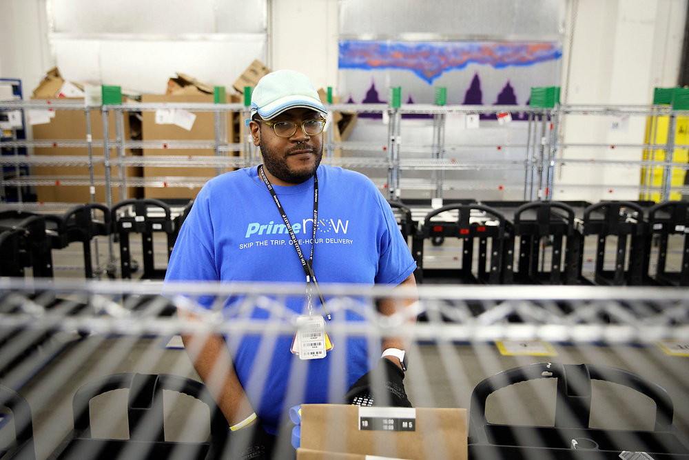 Ryan White, Amazon associate, stands for a portrait as he fills shopping bags with products for customers orders at the Amazon.com Inc. Prime Now fulfillment center warehouse on Monday, March 27, 2017 in Los Angeles, Calif. The warehouse can fulfill one and two hour delivery to customers. Complex supply chains such as Amazon's and e-commerce trends will impact city infrastructure and how things move through cities. © 2017 Patrick T. Fallon