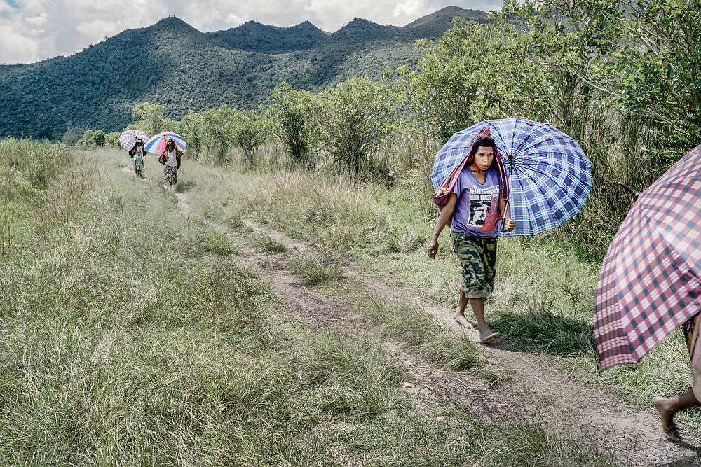 Women from Pugima, a village in the Baliem Valley, are seen walking home.  Only vehicles with 4-wheel drive could navigate through the difficult terrain.<br />