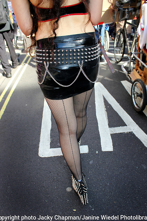 Woman walking in street with fishnet tights and short laytex skirt