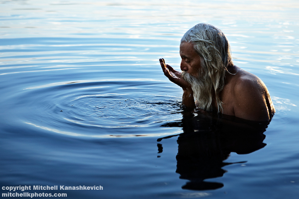 Indian culture - An Indian holy man taking a sip from the holy waters of the Narmada River, Maheshwar, Madhya Pradesh, India,Traditions and culture