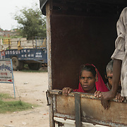 Travelers catch a ride however they can - in this case, crammed with a dozen others in the back of a pickup truck in the rural lands of Uttar Pradesh, India.