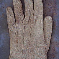 Victorian childs beige cotton glove lying palm down on rusty metal sheet