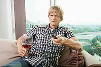 Displeased mid-adult man with wine glass watching television on sofa at home