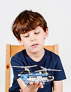 Young boy plays with a self constructed toy helicopter