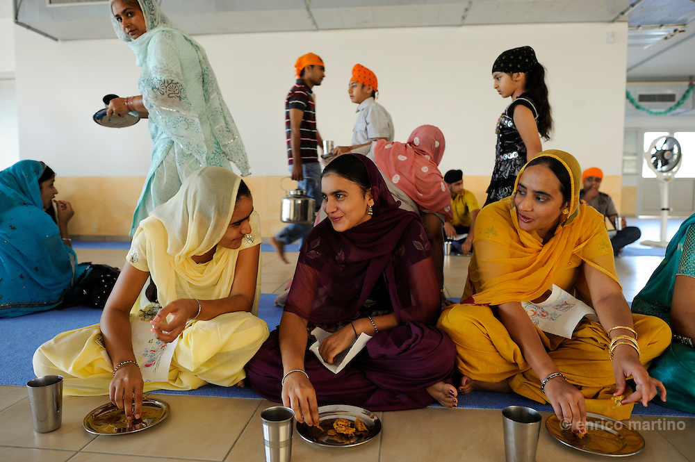"Pessina Cremonese. Sikh believers eating and drinking on the ground floor of the temple. The establishment of ""Langar"" (common kitchen) serves to create social equality. The Sikh religion requires that the faithful have always the right to be fed."