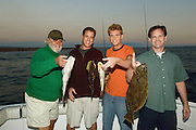 Family of Sport Fishermen Displaying Fish