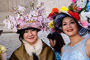 New York, NY - April 16, 2017. Two Asian women in elaborate hats on the steps of St. Patrick's Cathedral at New York's annual Easter Bonnet Parade and Festival on Fifth Avenue.