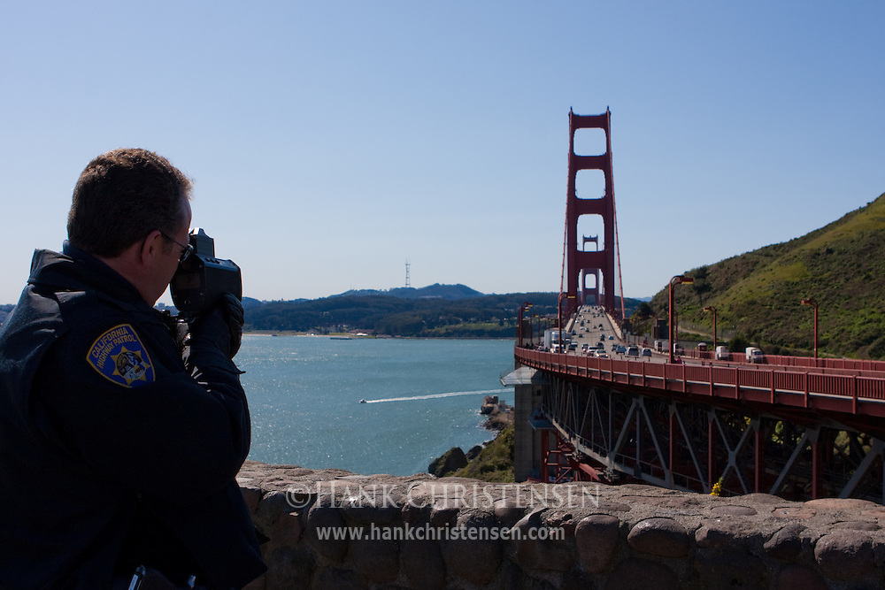 Policeman uses a radar gun to catch speeders crossing the Golden Gate Bridge