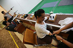 Aishah is helped to put on her bionic arm during practices at an air rifle range in Singapore, 20 June 2014. The bionic arm has to be adjusted often as sweat makes it slippery and sometimes hurt her when it slips off.