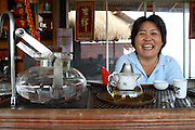 30 May 2007 - Mae Salong, Thailand - A young woman pours tea inside one of the first tea shops in Mae Salong. Photo credit: Luke Duggleby