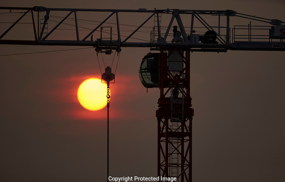 Red sun sets behind a building crane in Tacoma, WA, Sunday, Aug. 6, 2017. The sun is red due to forest fire smoke drifting in from British Columbia. (Photo/John Froschauer)