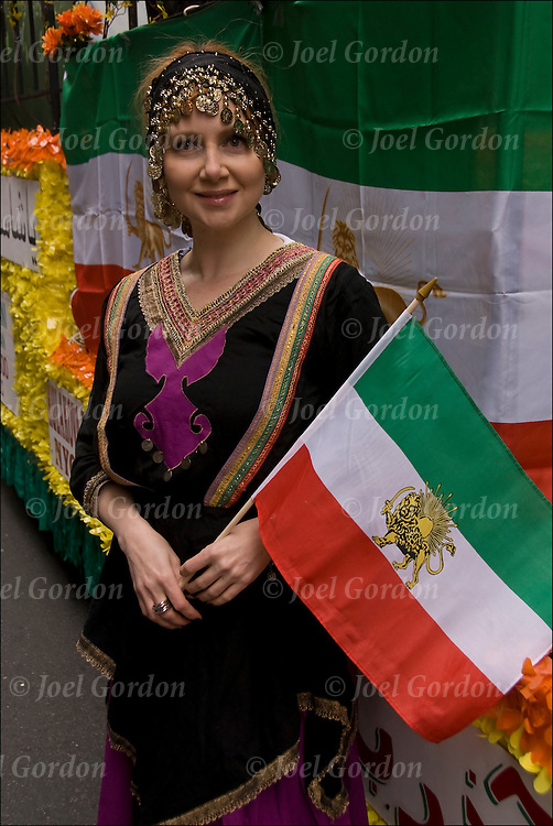 Portrait of smiling  Iranian American young woman holding Iranian flag, dressed in transitional folk costume from Kourdestan in northern Iran showing her ethnic pride, before the start of the 2011 Persian Iranian Parade in New York.