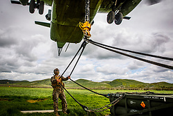 U.S. Marine Corps Sgt. Troy Yakin, landing support specialist, Headquarters and Service Company, Combat Logistics Battalion 1, Combat Logistics Regiment 1, 1st Marine Logistics Group, secures a rope to the static hook of a CH-53E Super Stallion helicopter during a sling loading drill at the Tactical Aircraft Landing Area, Marine Corps Base Camp Pendleton, California, March 21, 2019. Sling loading is a heavy lift method used to transport a variety of equipment, vehicles and other assets in an expedient and efficient manner. CLB-1 was conducting the drill as a part of training preparation for an upcoming deployment. (U.S. Marine Corps photo by Cpl. Dylan Chagnon)