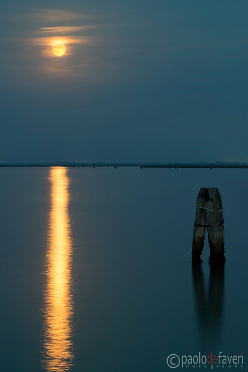 Thu full moon of mid October rising over the placid waters of the Venetian Lagoon. Taken from the waterbus stop of Burano