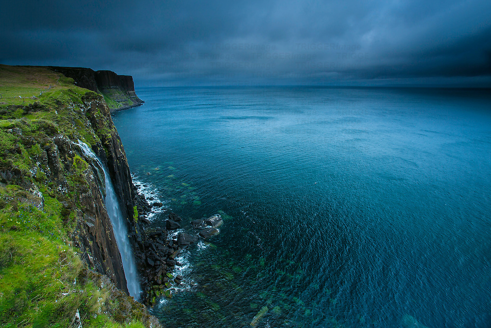 Hi view from cliff top of waterfall in Scotland to the north sea with stormy sky