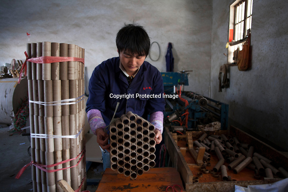 Hunan, Liuyang, Dec. 19..2013 :  Luo Yong m, a worker in a firecracker factory , assembles tuves of fireckrackers which later on will be decorated and filled with dynamite.