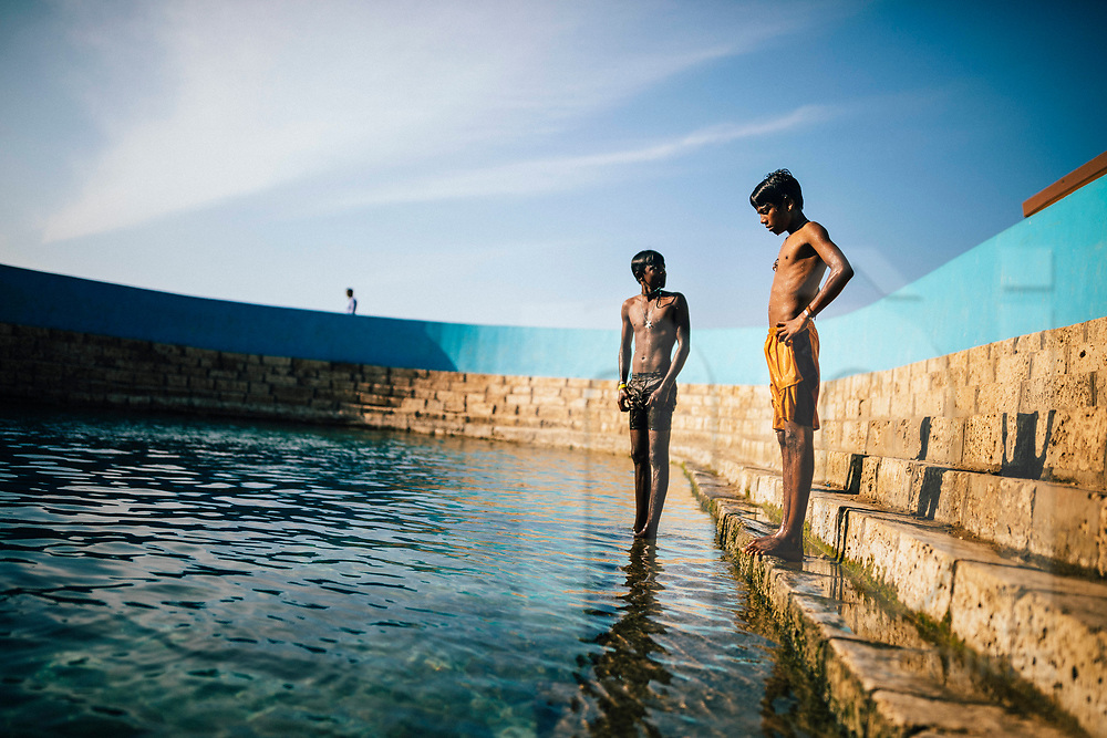 Young boys at the Keerimalai Springs, sacred pools fed by sea waters on the northern shores of the Jaffna Peninsula, Sri Lanka, Asia