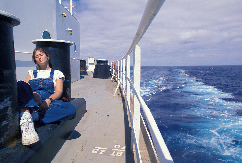 USA, Alaska, Second mate Karen Devine naps in summer sun aboard Oil tanker Arco Juneau sailing for San Francisco, CA