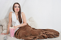 Beautiful young woman having popcorn while sitting in bed