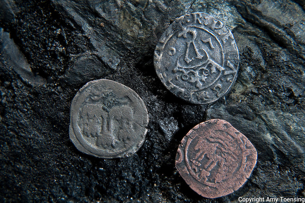 ORANJEMUND, NAMIBIA -- OCTOBER 05: Coins that archeologists presume to be pocket change for sailors on the Portuguese ship discovered on site October 05, 2008 in Oranjemund, Namibia. The wreck was discovered by miners in the Namdeb diamond mine off the coast of Namibia. The ship was found seven meters below sea level on April 1, 2008. Archeologists presume the wreck is from the early 1500s. Most of the the artifacts found are being stored in a storage shed at the Namdeb Diamond Mine. Items include: copper ingots, bronze canons, canon balls, pewter bowls and plates, ivory tusks from African elephants, and most substantial over 2000 gold coins- approximately 21 kg - the most gold found in Africa since the Valley of the Kings in Egypt. (Photo by Amy Toensing) _________________________________<br /> <br /> For stock or print inquires, please email us at studio@moyer-toensing.com.