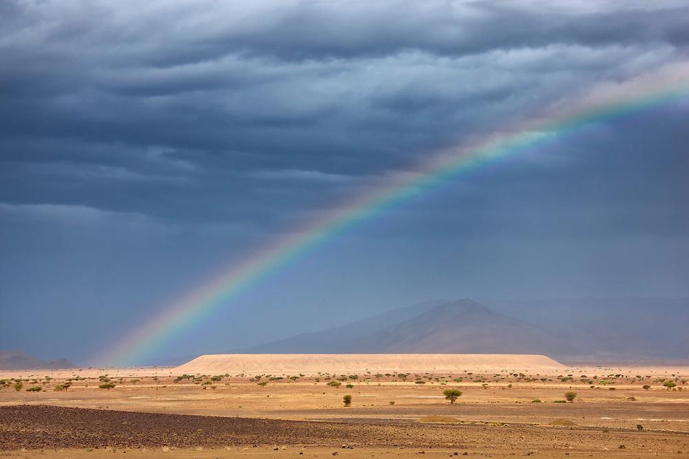 Dark clouds and rainbow in the Sahara desert.