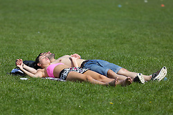 © Licensed to London News Pictures. 04/05/2016. Leeds, UK. A man and a woman bathe in the bright warm sunshine in Hyde Park in Leeds, West Yorkshire. Britain is experience warmer weather this week with temperatures to rise to 23 degrees celsius this weekend. Photo credit : Ian Hinchliffe/LNP