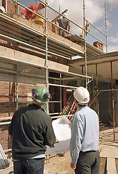 Architect and Site Manager check progress of bricklaying on housing development Haringey North London