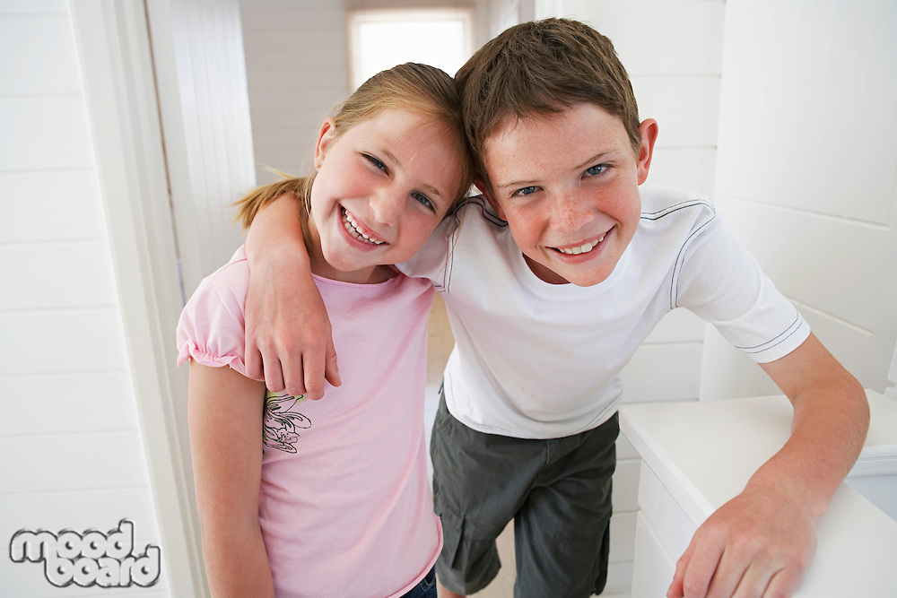 Young boy with arm around young girl in white room