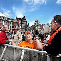 Nederland, Amsterdam , 28 april 2013.<br /> Voorbereidingen en opbouw van de media op de Dam Koningsdag 30 april.<br /> De NOS heeft een glazen huis op de Dam geinstalleerd van waaruit verslag zal worden gedaan tijdens de Kroningsdag.<br /> De nodige voorbereidingen worden getroffen. Kabels worden aangebracht, perstribunes opgebouwd etc.<br /> Op de Foto: Achter de hekken op de Dam trekt inmiddels al heel veel nieuwsgierig koningsgezind publiek zoals de Venezuelaanse vrouw, die zich voordoet als prinses Maxima.<br /> Preparation and build up the media at the Dam in Amsterdam for King's Day, April 30th.<br /> The NOS installed a glass house at the Dam from which they will be broadcast at the King's Day. The royalist audience is already there.
