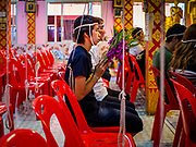 "29 MARCH 2017 - BANG KRUAI, NONTHABURI, THAILAND: A man prays during a ""Resurrection Ceremony"" at Wat Ta Kien (also spelled Wat Tahkian), a Buddhist temple in the suburbs of Bangkok. People go to the temple to participate in a ""Resurrection Ceremony."" Thai Buddhists believe that connecting people by strings around their heads, which are connected to a web of strings suspended from the ceiling, amplifies the power of the prayer. Groups of people meet and pray with the temple's Buddhist monks. Then they lie in coffins, the monks pull a pink sheet over them, symbolizing their ritualistic death. The sheet is then pulled back, and people sit up in the coffin, symbolizing their ritualist rebirth. The ceremony is supposed to expunge bad karma and bad luck from a person's life and also get people used to the idea of the inevitability of death. Most times, one person lays in one coffin, but there is family sized coffin that can accommodate up to six people. The temple has been doing the resurrection ceremonies for about nine years.          PHOTO BY JACK KURTZ"