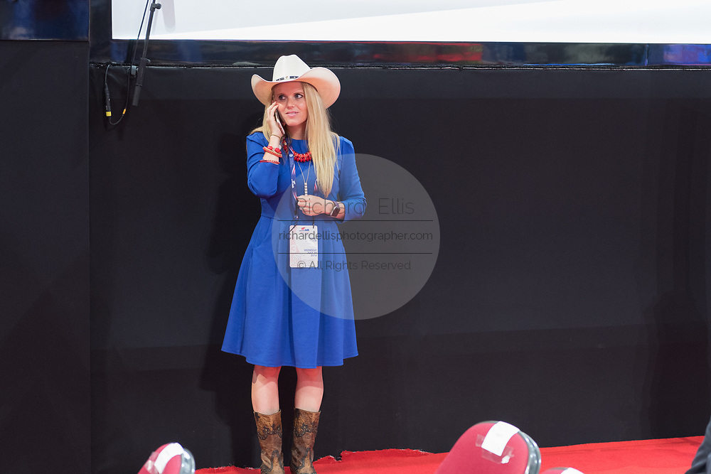 A GOP delegate from Texas in a cowboy hat and boots talks on her mobile phone during the Republican National Convention July 20, 2016 in Cleveland, Ohio.