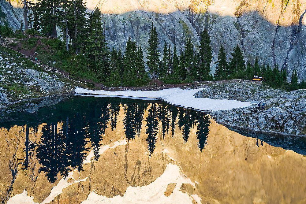 Hikers are reflected against Mount Shuksan as they walk along  the shore of Lake Ann in Mount Baker-Snoqualmie National Forest, Washington.