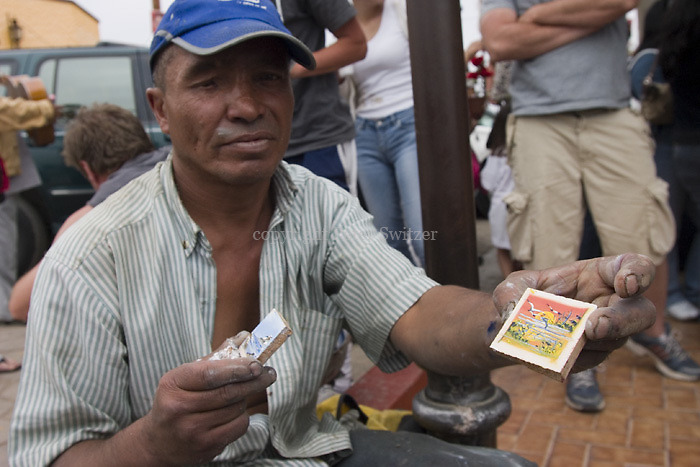 A man creates miniature paintings and sells on the street in Puerto Nueva Mexico June 3, 2007.