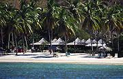 beach restaurant, steel band; thatched umbrellas, people relaxing; aqua water; Peter Island; British Virgin Islands