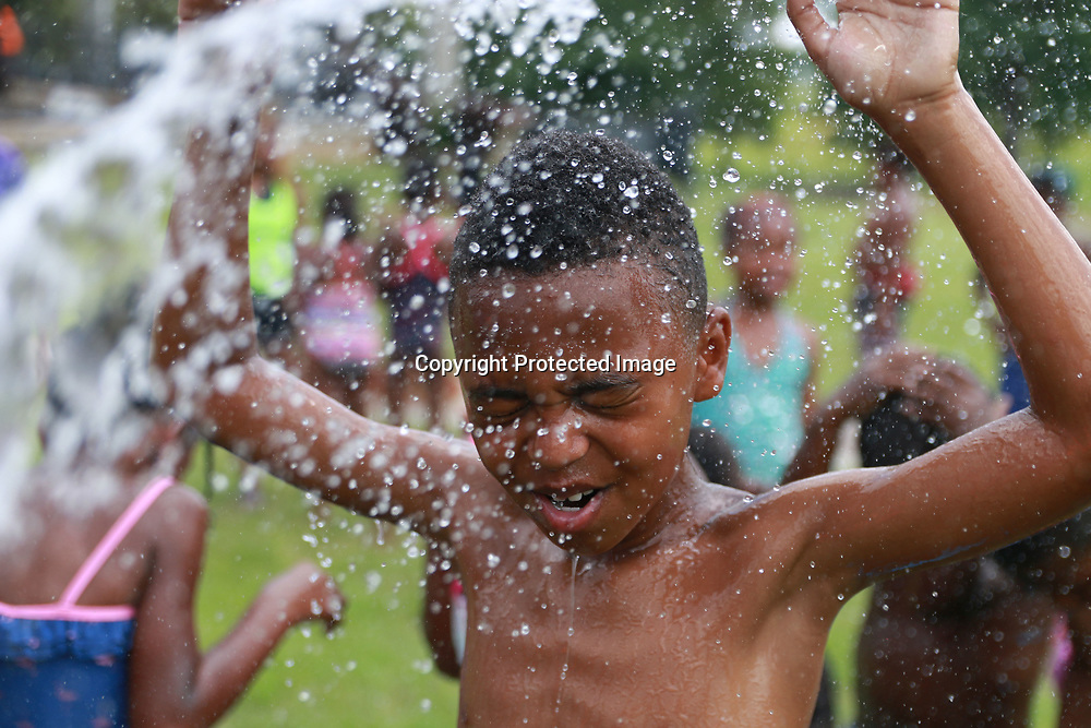 10-year-old C.J. Witherspoon cools off from the heat of the midday sun by getting splashed with water from a garden hose courtesy of one of the camp counselors.