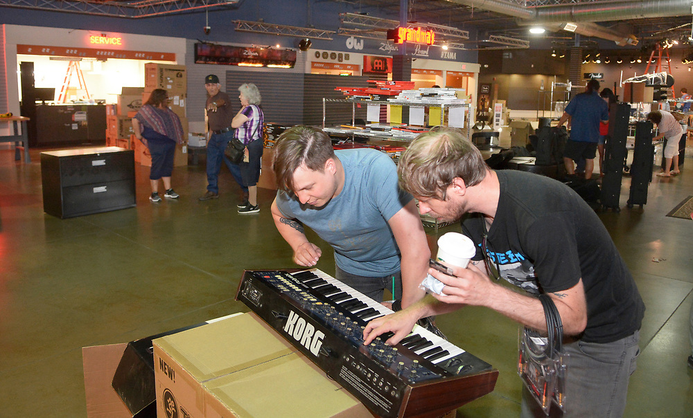 gbs073117b/BUSINESS -- Dustin Casteel (cq) and Will Phillips look a keyboard in the nearly empty showroom of Grandma's Music & Sound. The store at 9310 Coors Boulevard NW is closing its doors after 34 years in business. (Greg Sorber/Albuquerque Journal)