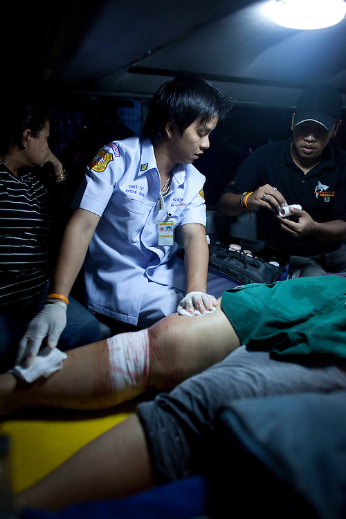 A volunteer ambulance worker treats the victim of a grenade attack in Klong Toey market, Bangkok..Ruamkatanyu is a private Thai charity funded by donations. It's members are volunteers who using their own customised vehicles to respond to road accidents, suicides, fires, bar fights and anything else involving death or injury. With varying degrees of medical training they try to stabalize the injured before transporting them to hospital or in the case of deaths take the bodies to the morgue. These volunteer ambulance crews have been nicknamed 'The Body Snatchers'.