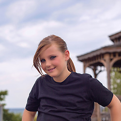 Portrait of a young biker, near a gazebo by the lake.