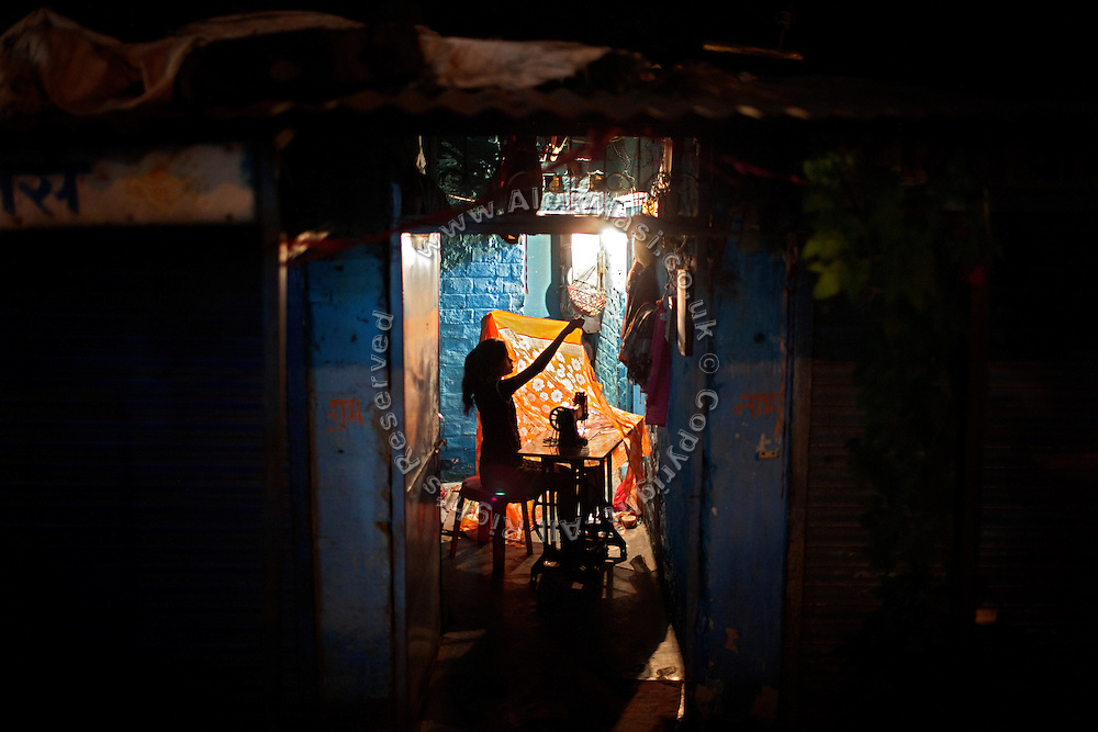 A young woman is sawing an orange sheet inside her home in Arif Nagar, one of the water-affected colonies in Bhopal, Madhya Pradesh, India, near the abandoned Union Carbide (now DOW Chemical) industrial complex, site of the infamous 1984 gas tragedy. The poisonous cloud that enveloped Bhopal left everlasting consequences that today continue to consume people's lives.