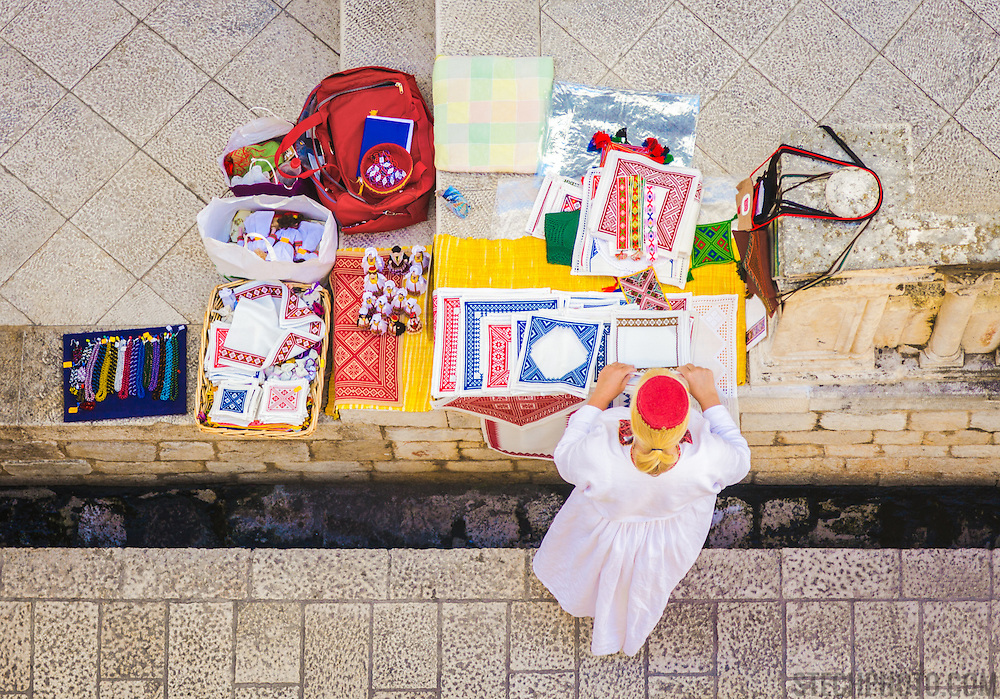 A birds eye view of a vendor in Dubrovnik, Croatia, setting up her crafts and wares for sale in the morning before tourists arrive in the old city walls.