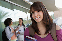 Female student holding book at school, smiling