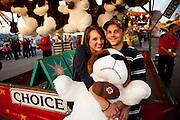 A couple celebrates winning a giant stuffed animal during a skill game at the South Carolina Coastal Fair in Charleston, SC.