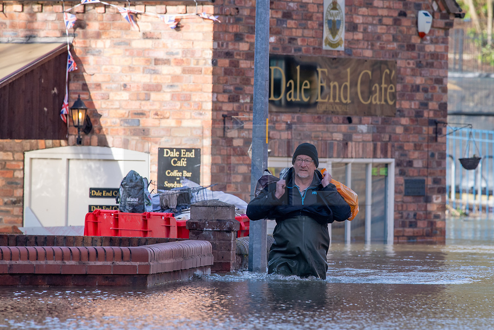 © Licensed to London News Pictures. 26/02/2020. Ironbridge, UK. A man walks in waist deep water in Ironbridge as flood defences were breached on part of the River Severn as levels continued to rise police evacuated part of the town. Photo credit: Peter Manning/LNP