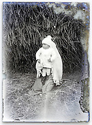 eroding glass plate with toddler held by older child in front of haystack
