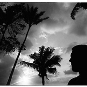 A man is silhouetted near palm trees on the of island Oahu in Hawaii.