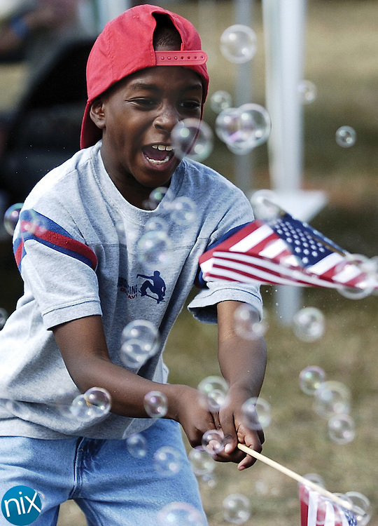Jalen Walker, 8, tries to pop bubbles at the Midland Magic Festival Saturday afternoon.