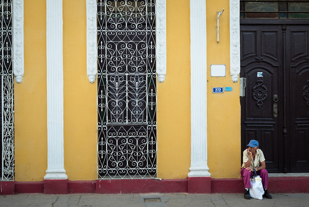 Man sitting in doorway of a colourful building in Trinidad, Cuba