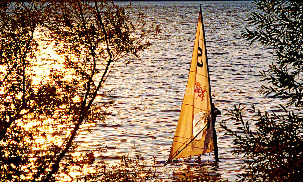 Windsurfing on a lake in Chambery, France at sunset. SPORT